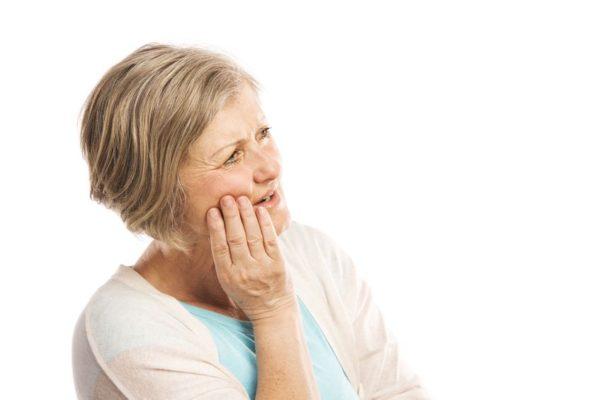 Kiefergelenkarthrose - Frau mit Schmerzen im Kiefer