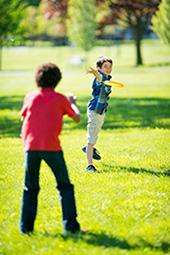 Kinder spielen draussen Frisbee im Garten oder Park um ihre Bewegung zu fördern