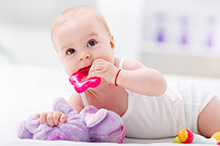 Baby mit Body und Strampler liegt auf Wickeltisch mit Beißring im Mund