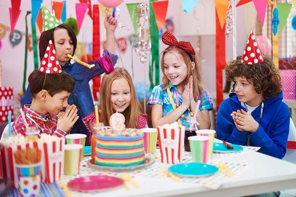 Kinder mit Geburtstagstorte auf Kinderparty